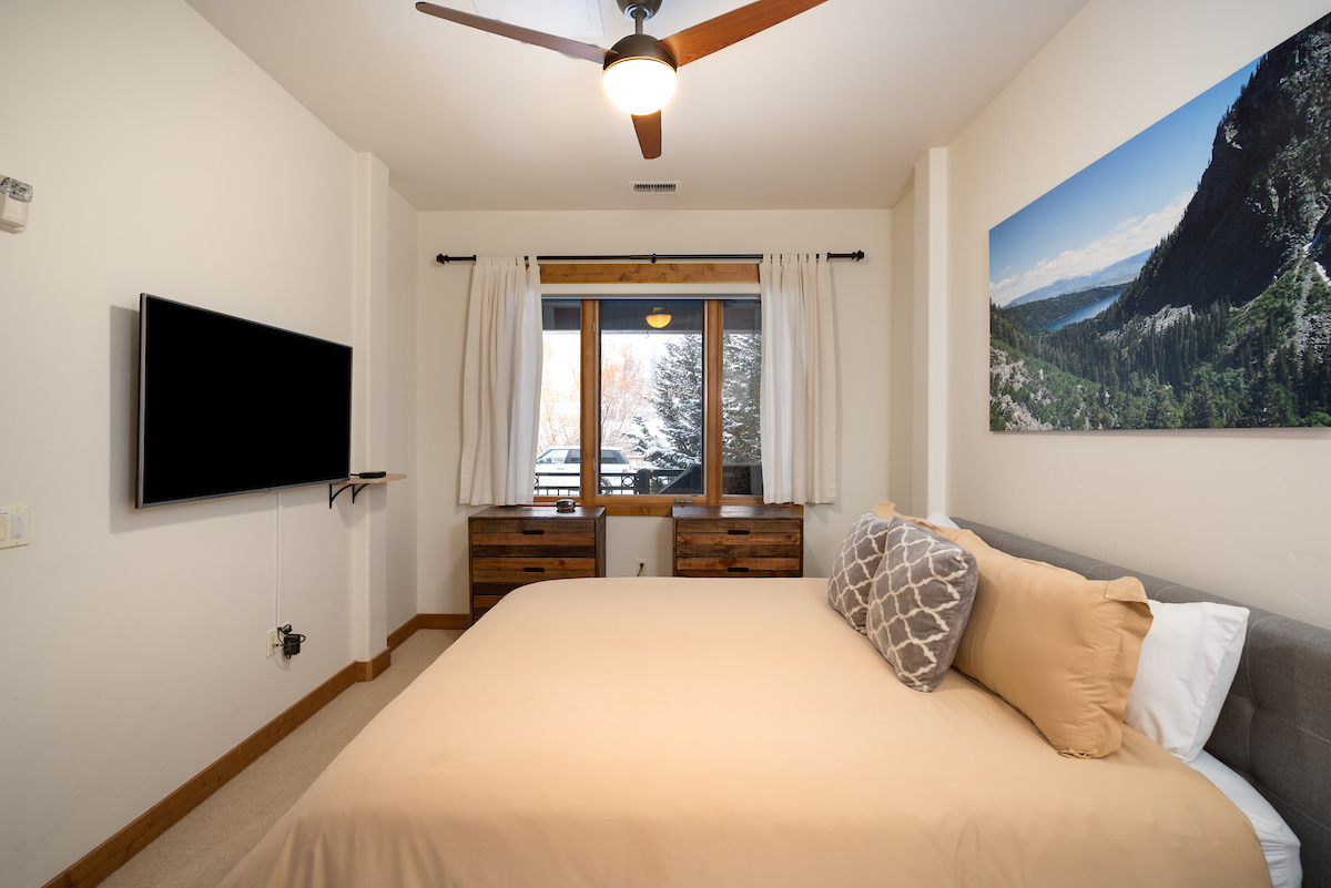 Master bedroom with ceiling fan and TV