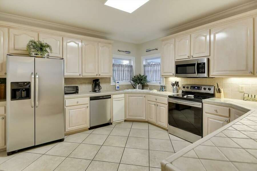 Extra Spacious Kitchen is Fully Equipped with Stainless Appliances and Tiled Counter Tops.
