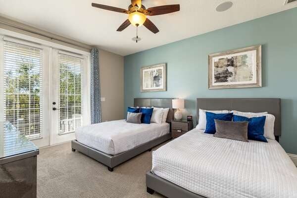 This relaxing bedroom features two full bedfs and balcony access