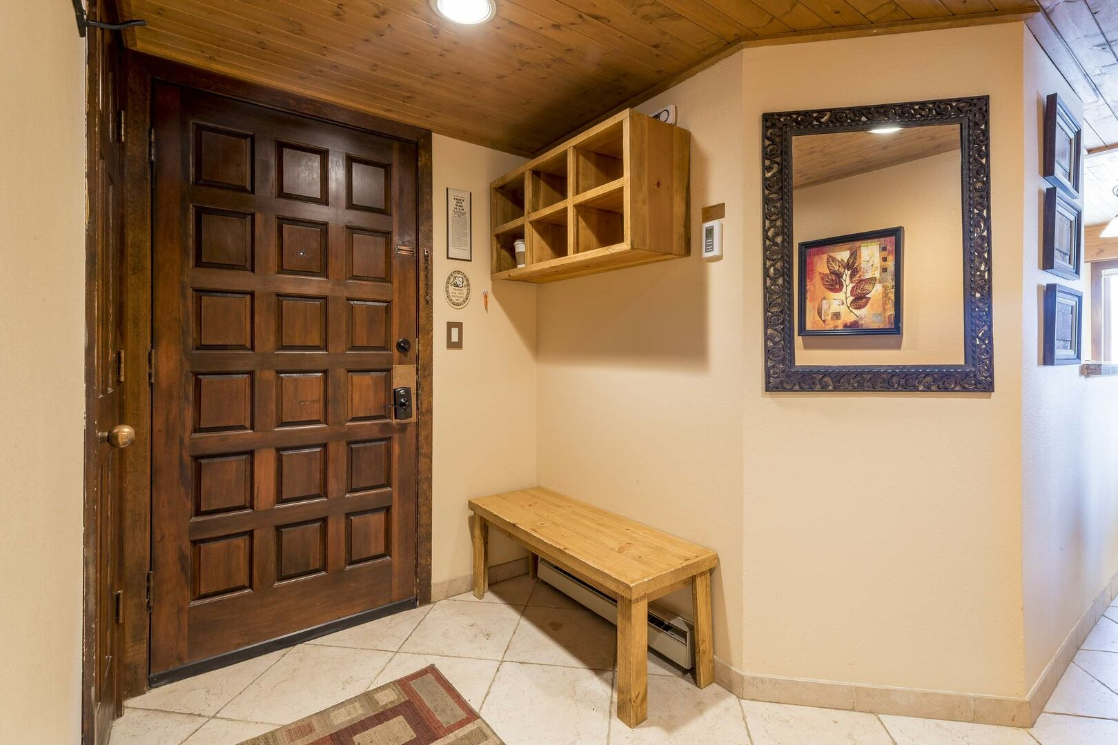 Entry with storage cubbies, bench and a hidden laundry room.