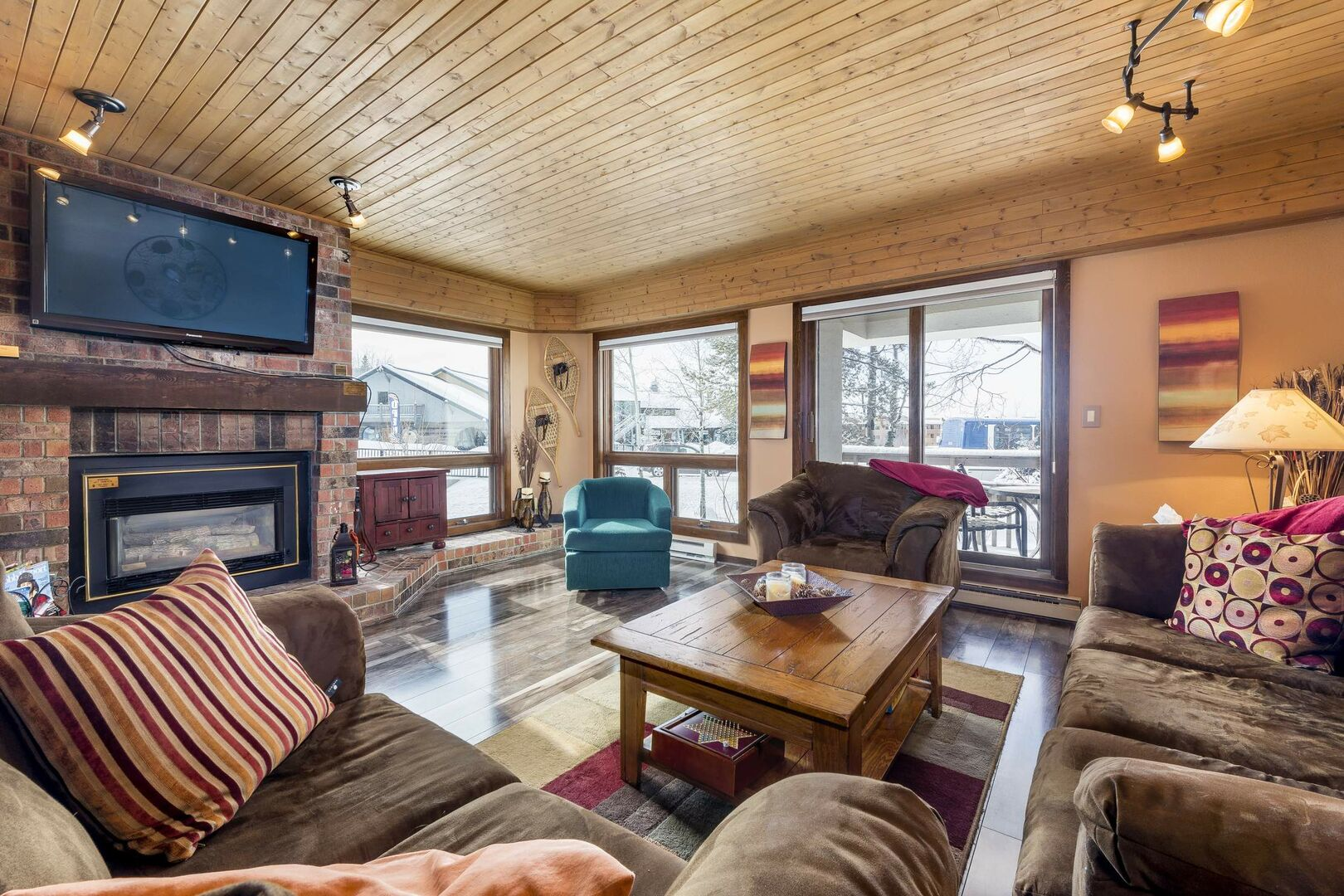 The living area incorporates exposed brick and natural wood, with a large TV, gas fireplace and the entrance to the deck.