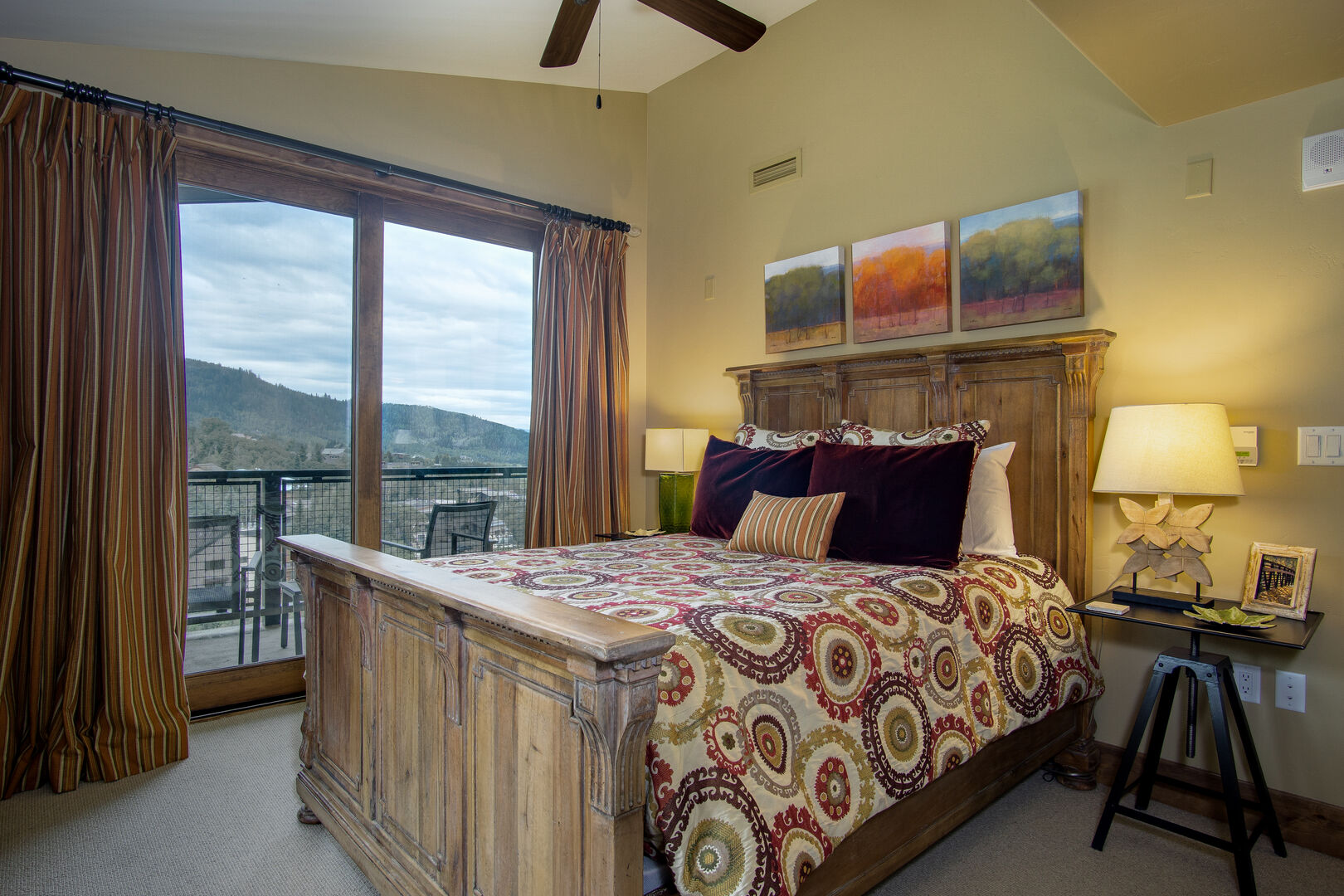 Bedroom with Large Bed, Nightstands, Ceiling Fan, and Sliding Doors to the Balcony.