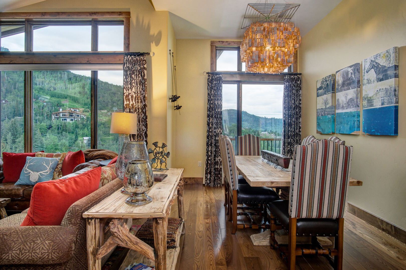 Dining Table, Chairs, Sofa Table, Sofas, and Windows with Mountain View.