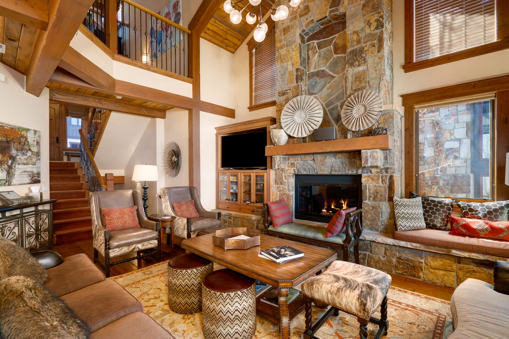 Living space with stone surround gas fireplace and TV.