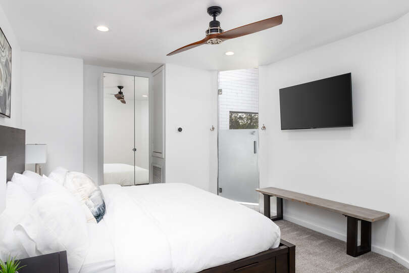 Large Bed Facing Television Mounted on Wall.