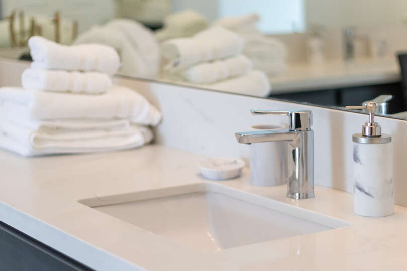 Image of Neatly Folded Towels on Bathroom Counter.