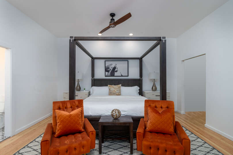Image of Large Bed and Two Accent Chairs in Bedroom.