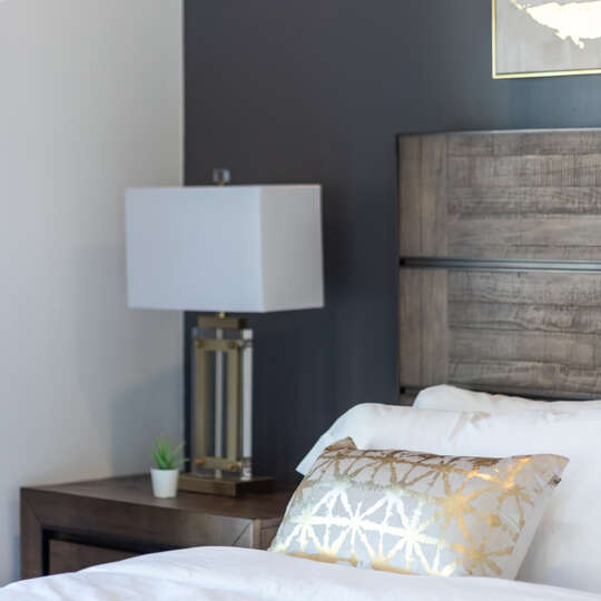 Side Table, White Lamp, and Wooden Bed in Bedroom.