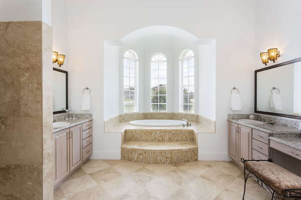 Elegant ensuite master bathroom with personal vanity areas