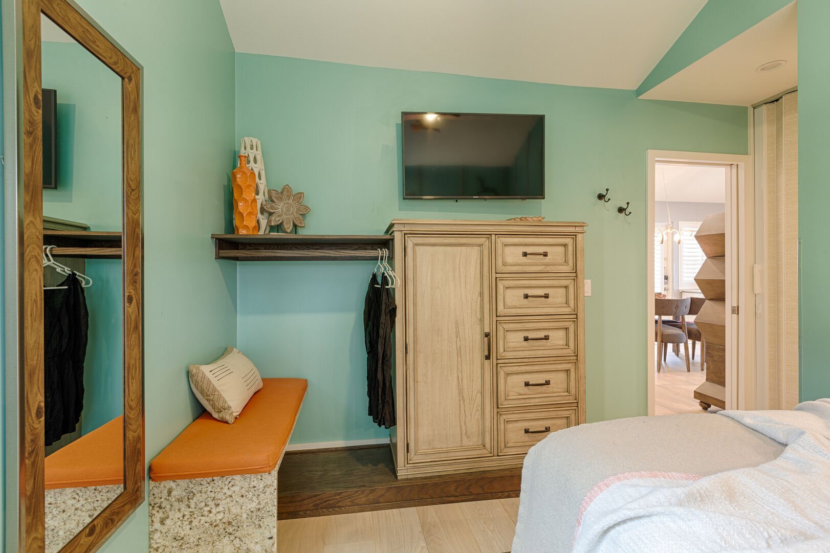Mirror, TV, and Tall Dresser in a Bedroom