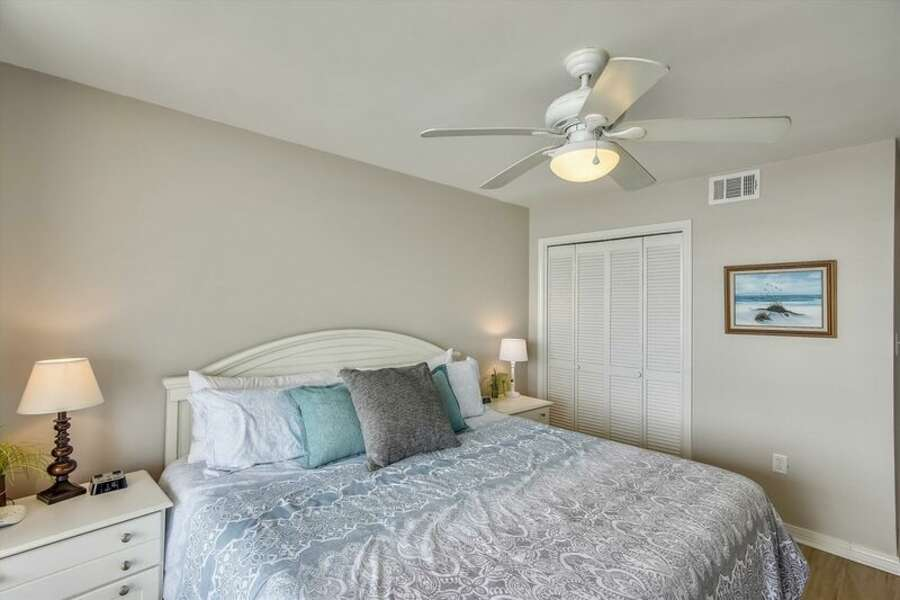The master bedroom has a king size bed with private balcony access.