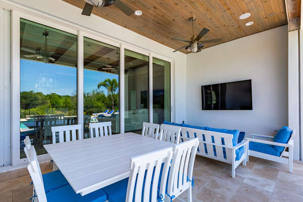 Enjoy the lanai featuring a 75-inch TV, table and sofa seating that can accommodate up to 10 guests