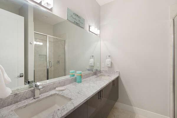 Sleek ensuite bathroom with a dual vanity and walk in shower