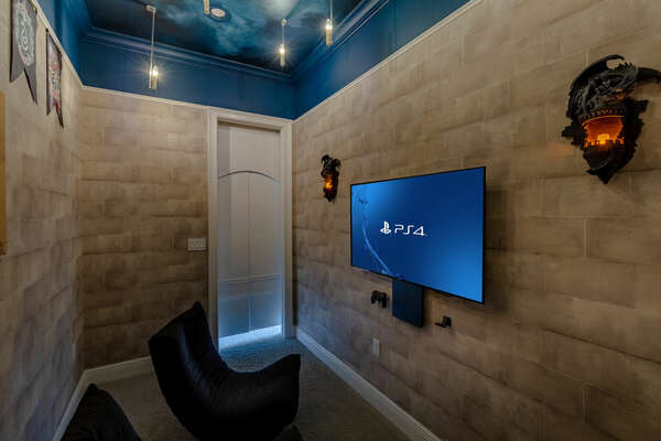 Inside is a large TV, Playstation 4  and 3 gaming chairs