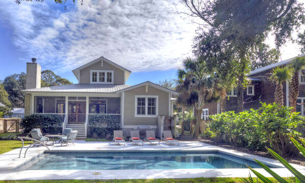Pool, pool chairs, and a view of the back exterior of this house to rent in St. Simons Island GA.