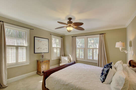 Bedroom with large bed, armchair, and ceiling fan.