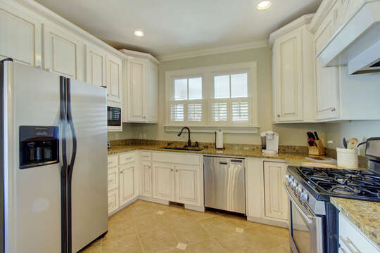 Fridge, sink, oven, and ample cabinetry in the kitchen of this house to rent in St. Simons Island GA.