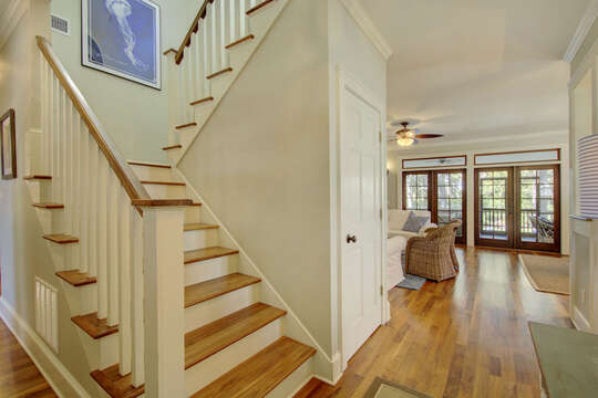 Entryway with stairs leading to upper floor and view of living area.