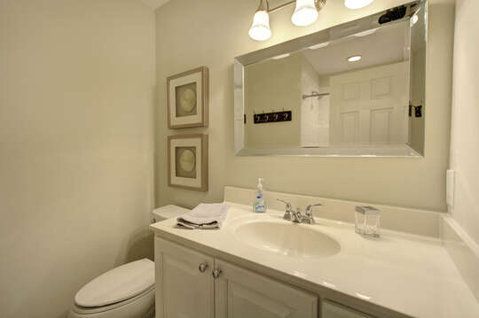 Bathroom with large mirror, sink, and toilet.