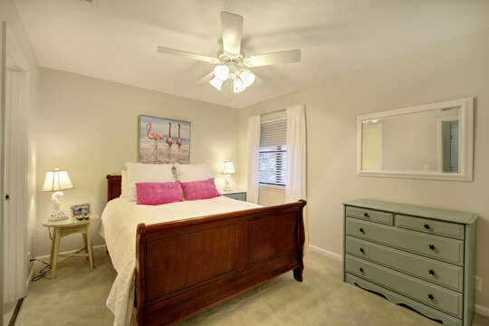 Bedroom with large bed, twin nightstands, and a dresser with mirror hung above it.