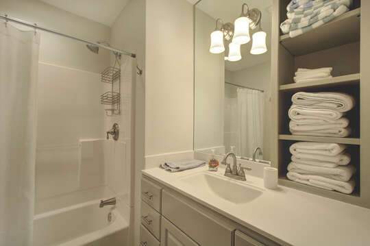 A shelf of towels sits on top of the sink counter beside a mirror and the shower.
