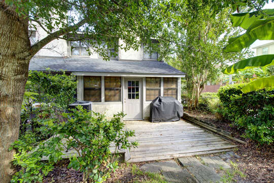 An angled photo of the backyard of this accommodation in St. Simons Island GA, highlighted by trees and bushes.