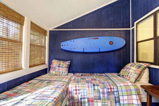 Two beds lay next to each-other in a L-shape below a surfboard.