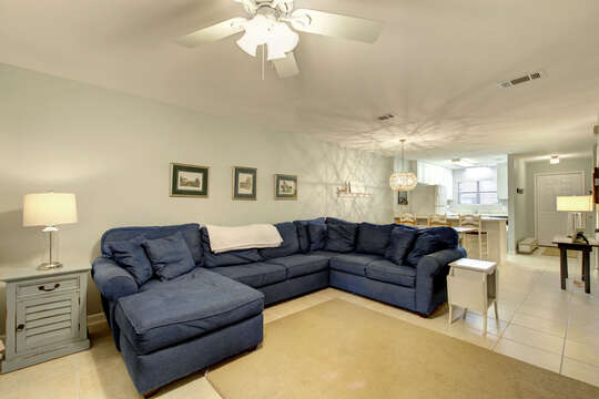 A wide photo of the blue sectional couch of this accommodation in St. Simons Island GA, with side table next to it and a view of the kitchen.