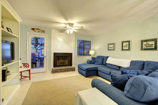 Living area with a blue sectional couch, fireplace, and TV.
