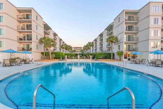 Pool, Outdoor Tables, Table Umbrellas, Chairs, and the Condominium Buildings.