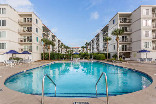 Pool, Patio Tables, Chairs, and the Condo Buildings.