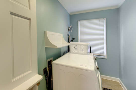 Blue Laundry Room Features Large Window.