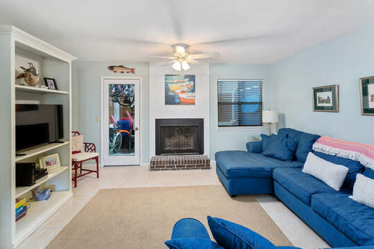 Living area with fireplace, a blue sectional couch, and large TV on shelf with other decor.