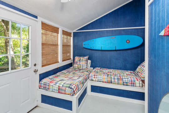 Side room of this accommodation in St. Simons Island GA, with two beds in a L shape and surfboards on the walls.