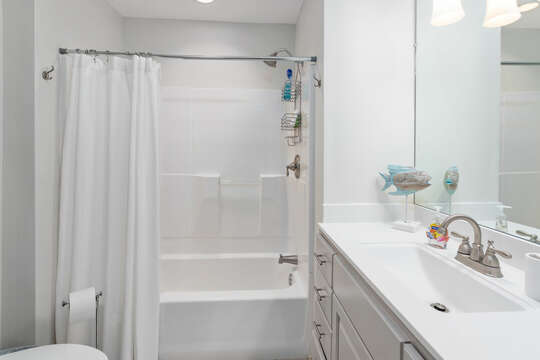 Bathroom with shower (curtain open), sink with mirror, and toilet.