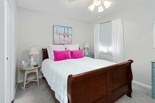 Bedroom with large bed, twin nightstands, and colorful decor.