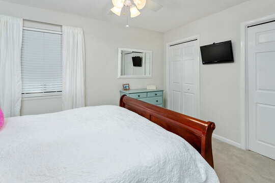 Another angle of a bedroom with large bed, dresser, mirror, and wall-mounted TV.