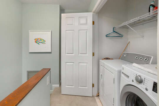 Laundry space on the upper floor complete with washer and dryer behind a set of double doors.