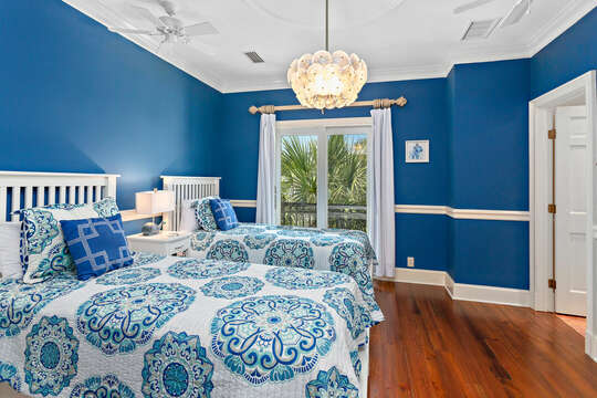 Blue Bedroom Includes Two Beds and Hanging Light Fixture.