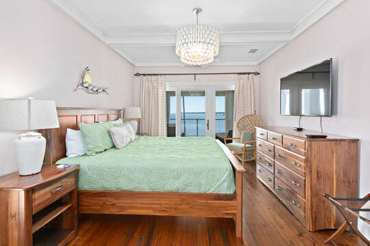 Large Bedroom Has Wooden Furnishings and TV.