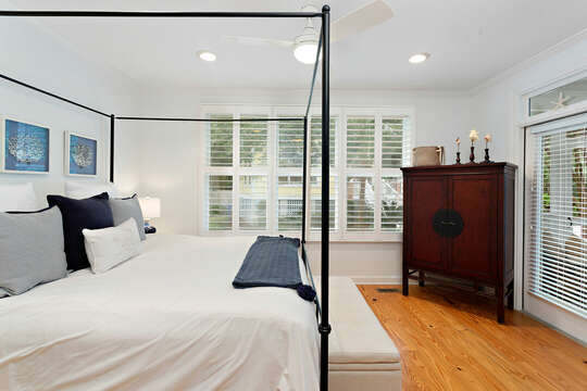 Master Bedroom with television, white walls and ceiling fan