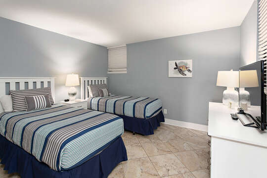 Guest bedroom with two twin beds and an HD TV