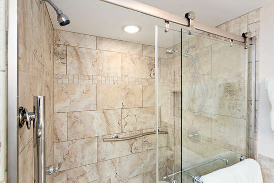 Large walk-in shower with two shower heads, seat and a hand held shower