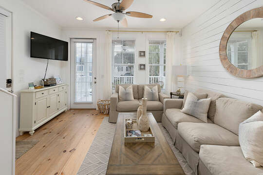 Living room with two couches, HD TV, access to porch and a central coffee table