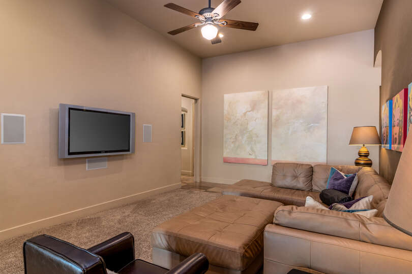 Room with couch, ottoman, and wall mounted TV