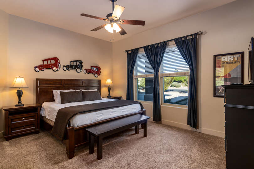 Bedroom with two windows, night stand and ceiling fan