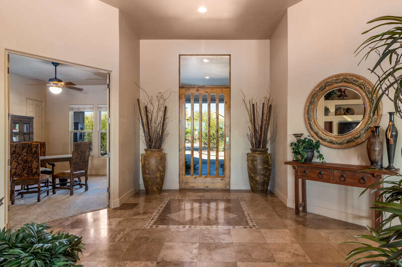 Foyer with glass door and nearby table and bookshelf