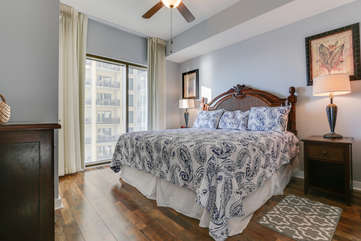 Bedroom with wood-grain vinyl plank floors.  King size bed and plenty of storage.