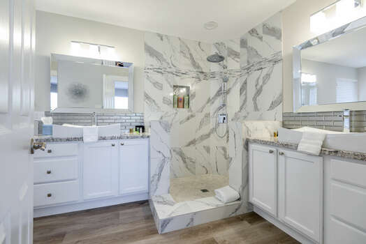 Stunning Master Bath with Dual Granite Countertop Vanities, a Marble Shower and a Soaking Tub