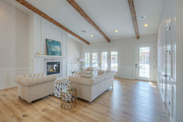 Formal living room with wood ceiling beams exudes grace, charm and style